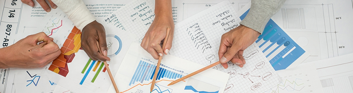 Image of hands holding pencils pointing at graph and visual metrics